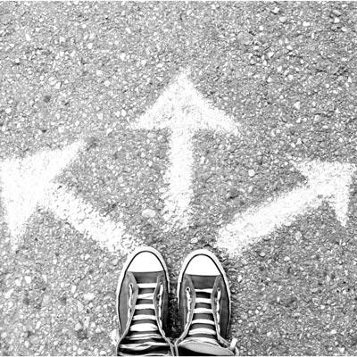 Ansicht von oben auf Straße, auf der 3 Pfeile mit Kreide gemalt sind. 1 Paar Schuhe stehen vor den Pfeilen, sinnbildlich für die verschiedenen Therapieformen, die je nach psychischen Problemen von Susanne Speer angewendet werden